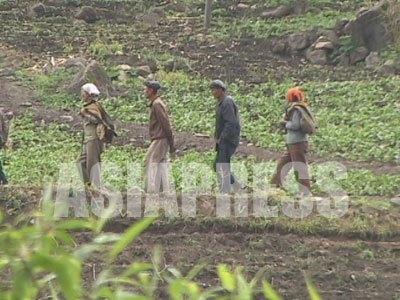 種まき前の草刈り作業に出てきた農民たち。山の斜面の狭い土地も利用する姿は痛々しい。(2005年4月 中国側から石丸次郎撮影)