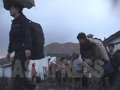 荷物を抱え、背負い、頭に載せて市場に向かう。03年4月に商行為が合法化されて後、一気に市場経済の拡大が進んだ。今や商行為抜きに北朝鮮の人々の生活は語れない。(2000年咸鏡北道茂山郡 チョン・チョルミン撮影)