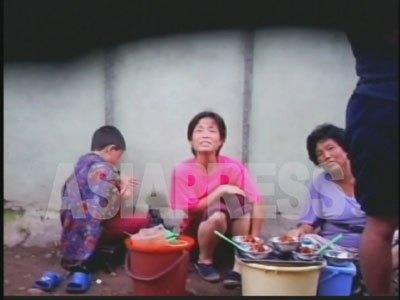 アパート街の路上で冷麺を売る女性たち。メットゥギ商売である。(2007年8月平壌市楽浪区域にて リ・ジュン撮影)