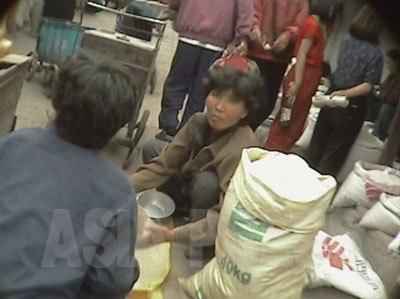毎年数十万トンづつ移入された韓国からの支援米が、横領された末に市場に横流しされて国民に供給される構造ができあがった。写真は清津の市場で支援米が売られている様子。(2004年7月 リ・ジュン撮影)