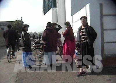 頭髪服装の取り締まりのために動員された女性同盟員たち。あまりやる気はなさそうだ。「資本主義の退廃文化浸透を打倒する」というお題目のためだろう、民族衣装のチマ・チョゴリを着て街頭に立っている。(2006年10月清津市 リ・ジュン撮影)