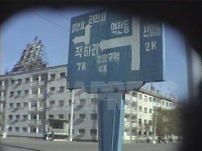 清津市中心の大通りの道路標識。中心部の幹線道路沿いのアパートは、見栄えを良くするために電気供給も良く値段が高いという。(2001年1月 キム・ホン撮影)