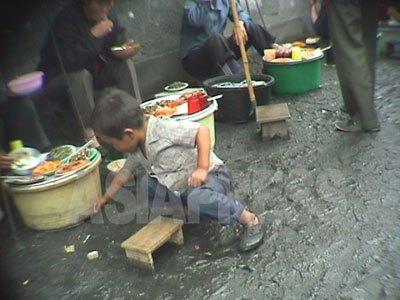 闇市場の露天食堂で客の食べこぼした米粒を拾う男児。90年代飢饉の際に全国どこでも見られた悲しい光景であった。(1998年10月江原道元山市 アン・チョル撮影)