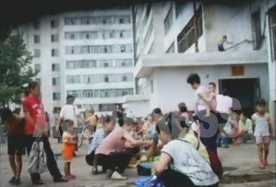 平壌市楽浪区域のアパート街の一角。住民たちがめいめい物売りをしている。(2007年8月 リ・ジュン撮影)