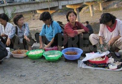 市場に向かう道で餅やパンなど自家製の食べ物を売る女性たち。別記事「内部記者が撮った! 北朝鮮最新事情 1」の若い兵士ほど痩せた人は見られない。商売で現金を得て食糧を買えるからだ(リンク先を参照した後この記事に戻るには、ブラウザの戻るボタンを押してください)。(2008年9月 チャン・ジョンギル撮影)