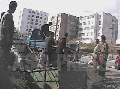 無許可で荷物運び商売をするリヤカーを没収する役人たち。(2008年10月海州市 シム・ウィチョン撮影)