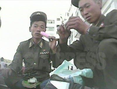 駅前でアイスキャンディーを食べる若い兵士。食糧の不足について不満を口にした。(2008年10月沙里院市 シム・ウィチョン撮影)
