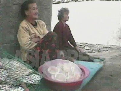 警備詰所の壁にもたれて商売する主人公のおばあさん。(2008年10月 シム・ウイチョン撮影)