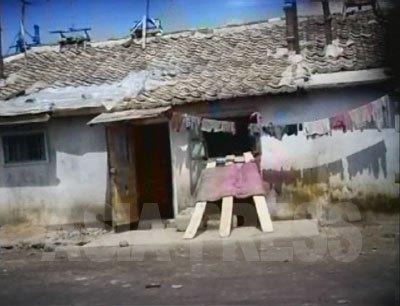 都市近郊にある「ハーモニカ」と呼ばれる長屋住宅の入口。屋根の上にテレビのアンテナが見える。(2007年8月黄海北道沙里院 リ・ジュン撮影)