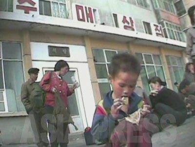 めぐんでもらった食べ物を口に運ぶ男の子。痩せている。(2008年9月沙里院 シム・ウィチョン撮影)
