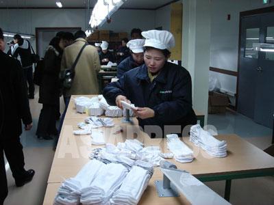 南北経済関係が冷え込む中で、開城工業団地は縮小されながらも運営が続けられている。外貨収入が乏しい北朝鮮にとっては貴重な収入源=甘い蜜に違いない。写真は工業団地の縫製工場で働く北朝鮮労働者。(2007年2月 アジアプレス取材班撮影)
