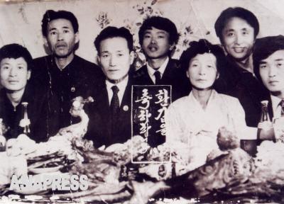キルスの祖父母の還暦祝いの写真.撮影は1993年とある。祖父の襟元には金日成バッジが見える。所狭し並べられた料理の半分ほどは「飾り」なのだという。