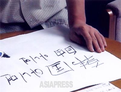UNHCR事務所内での籠城記者会見に備えて、家族全員がプラカードを書いた。「.韓国でなければ自由を、自由がなければ死を」と書いたのは最年少15歳のリ・ミンチョル。結局、記者はUNHCR事務所に入れず会見は行われなかった。 (撮影:石丸次郎)