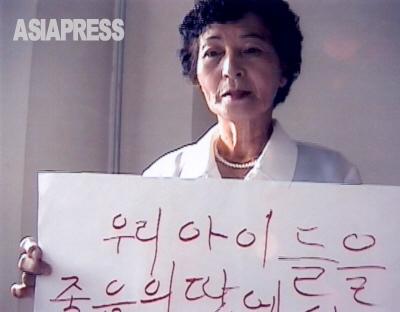 キルスの祖母・キム・チュノクさんは「子どもたちを死の地から救い出してください」と書いたプラカードを準備して北京のUNHCR事務所に入った。(撮影:石丸次郎)