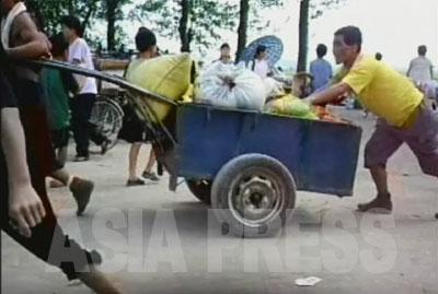 荷物運びや自転車修理、軽食販売など、市場での活動で現金を得ている人々にとっては、市場が混乱することは生活への打撃に直結する。写真は黄海北道沙里院(サリウォン)市の市場で荷役をする人。(2007年8月 リ・ジュン撮影)