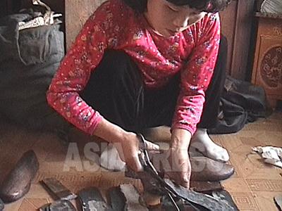 軍靴工場から盗んできた材料で靴を家内製造する女性。平安北道朔州(サクジュ)郡。朔州の家内手工業による靴製造は全国的に有名だ。(2006年7月 リ・ジュン撮影)