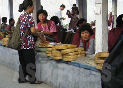 売場台に積み上げられているものが「人造肉」。帯状のものが巻かれて円盤になっている。北朝鮮の全国の市場でよく見かける食糧品だ。(2008年9月平壌市江東郡の公設市場 チャン・ジョンギル撮影)