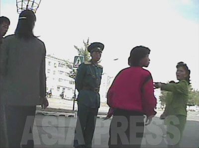 非を認めようとしない女性にいらついたのか、女性同盟の糾察隊員が罵り始める。(2008年10月海州市 シム・ウィチョン撮影)