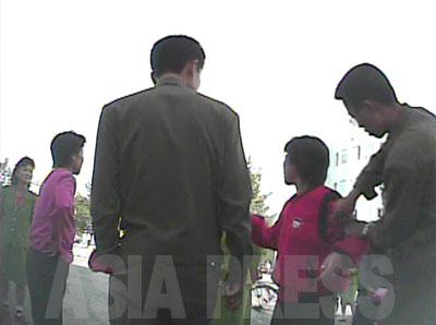 一歩も引かずに反撃する女性に業を煮やした糾察隊の男性が、女性の腕に「取締り」の腕章を付けようとしている。(2008年10月海州市 シム・ウィチョン撮影)