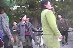 スカート姿の女性同盟の糾察隊員が、盛んに笛を吹きながら服装取締りをしている。自転車に乗っていていたり、ズボンをはいてるという理由で取締りに遭った人たちが一箇所に集められている。 (2008年10月沙里院市 シム・ウィチョン撮影)