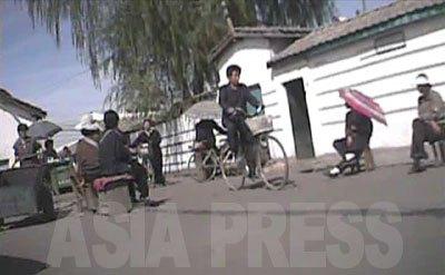 大成市場の門を背にして立つ。市場に連なる道路の両脇には、手に何かが書かれた紙を持った女性がずらりと並んで座っている。