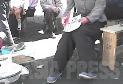 商品目録を書いた紙はタバコのカートンの堅い包装紙。取締り時にはパッと二つに折って隠す。シム記者を取締りの保安員と勘違いし、慌てて紙を閉じる女性の姿をカメラは捉えた。