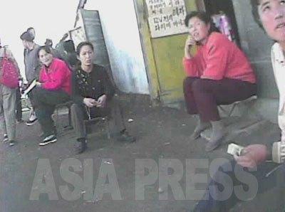 女性たちが座る背後の建物は、アパートに付属する倉庫だという。中国の古いアパートにも見られるが、北朝鮮ではアパートのそばに世帯ごとに使える倉庫がある。この倉庫が売買されて商品置き場となっているわけだ。店を開くと取締りがうるさいので目だった陳列はせず、目録で客を呼び込んで倉庫の中で商品を見せるのだ。