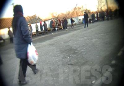裏通りの路地を抜けて広い通りに出る。ここからカメラは寺洞市場までは一直線に向かっていく。既に道の両側には、市場に向かう人目当てに商品を広げる人たちが大勢並んでいる。