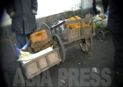 カメラは商売する人に近づいていく。リヤカーに積んで持ってきたのはソバ。トウモロコシやジャガイモなどを材料に家庭で作って売りに出す。