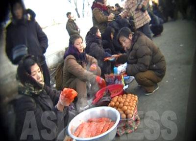 露天の食べ物屋で女性が腹ごしらえをしている。パンや餅などが売られている。写真手前のタライに入っている湯気の立った食べ物は何か不明。