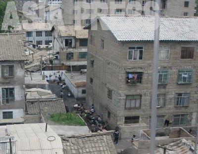 このアパート(写真右)は、外壁工事が未完成でペンキも塗られていないが、ほとんどの部屋は入居が済んでいるようだ。(2008年7月平安南道 ペク・ヒャン撮影)