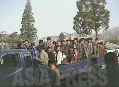 早朝、労働鍛錬隊の収容者がトラックに乗せられて労働現場に運ばれていく。男女両方の姿が見える。(2008 年9 月黄海南道海州市 シム・ウィチョン撮影)