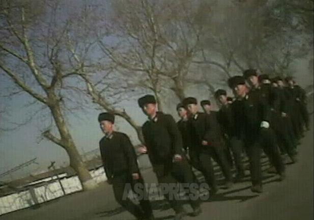 兵士たち40人ほどが隊列を組んで道の真ん中を行進している。しかし軍事バレードで見られるよ うな一糸乱れぬ行進ではなく、遅れ気味の者もいて、どこかのどかだ。