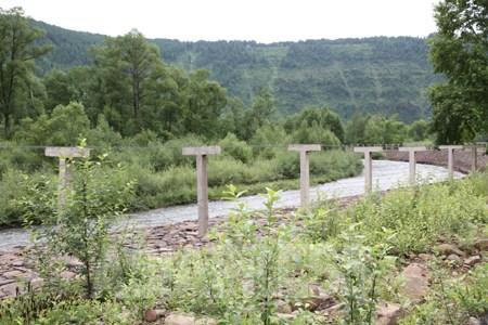 鴨緑江上流に張られた鉄条網は、美しい森林地帯にはえらく不釣り合いだ。2010年7月 李鎮洙撮影 (C)アジアプレス