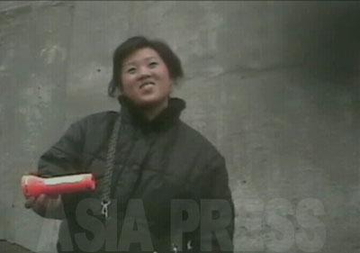 懐中電灯を撮影者に懸命に売り込む女性。笑顔で商品の魅力を語る。
