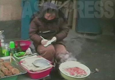 熱心に何かメモしている食べ物売りの女性。自家製のパンや餅や酒を売る。