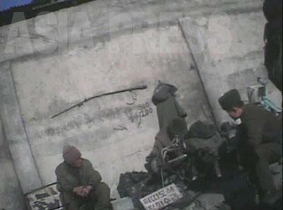 「革ベルト染色」「雑貨修理」と書かれた小さな看板を掲げ商売をしている男性。右手に座っている兵士は注文した作業が終わるのを待っているようだ。