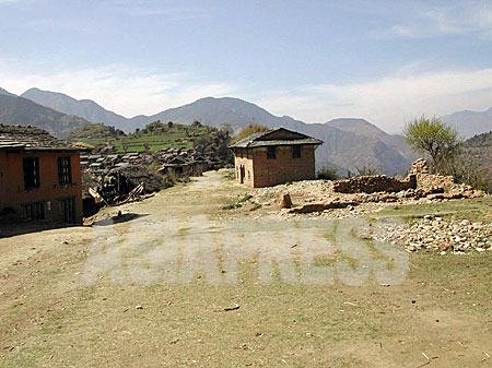 ルクム郡マハト村の集落。右手に見える残骸はマオイストの襲撃で破壊された警察詰め所。(2003年 3月8日 撮影 小倉清子)