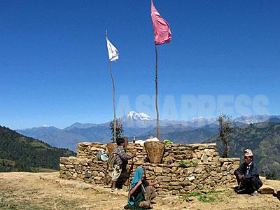 """タバン村に入る峠に作られチャウタラ(休憩所)に、赤い共産党の旗が立てられていた。遠くに見える白い山はルクム郡の5000メートル峰""""シスネ山""""。シスネ山はロルパ郡最高峰のジャルジャラ山とともに、マオイストの人民戦争のシンボルとされた。(2006年3月 撮影 小倉清子)"""