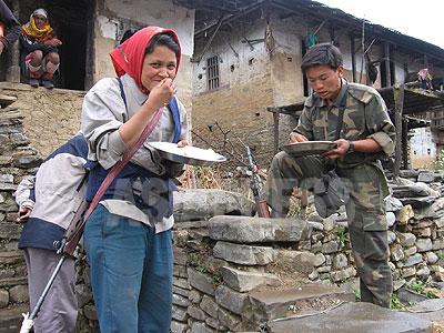 2006年3月、タバン村トゥーロガウンで立ったまま食事をする人民解放軍の女性ゲリラ。このころになると、写真撮影のときにゲリラは顔を隠すこともしなくなった。 (撮影 小倉清子)