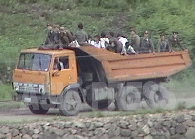 ダンプカーの荷台に軍人と住民が一緒に乗っている。軍人は金を払わないという。(1997年7月両江道恵山市 中国側より石丸次郎撮影)