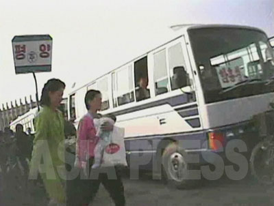 黄海南道海州市の鉄道駅のそばに出現したバスターミナル。看板には平壌とあり、右のバスのフロントガラスには咸鏡南道の咸興と行き先が示されている。300キロを越す長距離の移動になる。(2008年10月 シム・ウィチョン撮影)
