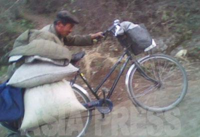 坂道を農村から買い出してきた食糧を運ぶ男性。都市の卸し商売人に売る。1キロ当たり30ウォン程度の利益にしかならず、貧しい都市住民がやる仕事だという。(2010年10月平安南道 キム・ドンチョル撮影)(上下ともキム・ドンチョル撮影)