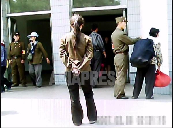 大きなリュックを背負っているとして兵士によって駅への入場を阻止される女性。 2011年6月 平壌市大城区域で ク・グァンホ撮影(アジアプレス)。