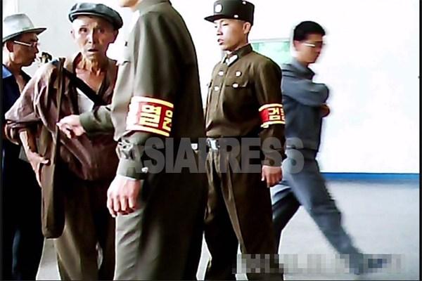 身なりがみずほらしいとして地下鉄駅への入場を兵士によって拒否される老人。 2011年6月 平壌市大城区域で ク・グァンホ撮影(アジアプレス)。