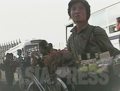 バス乗り場や休憩所には乗客目当ての物売りが集まってくる。中国の地方都市の光景とそっくりだ。女性は酒や飲料、果物、軽食、スルメなどを売っている。左隅にも車窓を見上げる物売りの姿が見える。(2008年11月黄海南道海州市 シム・ウィチョン撮影)