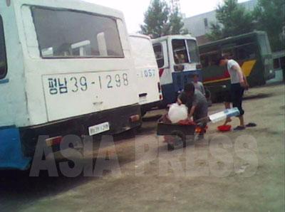 長旅を終えた乗客にリヤカーで運んだ洗面用の水を売っている。男性が足を洗っている。(2010年6月平安南道平城市 キム・ドンチョル撮影)