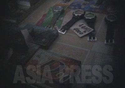 収買商店の中は薄暗い。サッカー、バスケット、バレーなどのボール、化粧品、運動靴、遊具、時計、ビデオテープなどが陳列されている。このような軽工業品はほとんどが中国製だ。スピーカーは撮影当時の金額で100ドル近くもするもので、庶民が手を出せるものではない。 リ・サンボン氏によると、収買商店では韓国ドラマや映画、成人もののDVDやCD-Rが密かに取引されていたこともあったという。