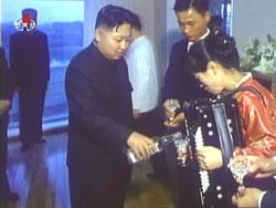 芸術家アパートを訪問し酒を注ぐ金正恩。金正日に同行したこの視察は記録映画になっている。(2010年10月 朝鮮中央テレビより)
