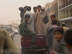 警察のトラックの荷台に乗せられ街中で見せしめにされる男たち。「女性に薬を飲ませて暴行を行った者」とトラックのスピーカーで罪状が読み上げられていた。(2002年・カンダハル・撮影:アジアプレス )